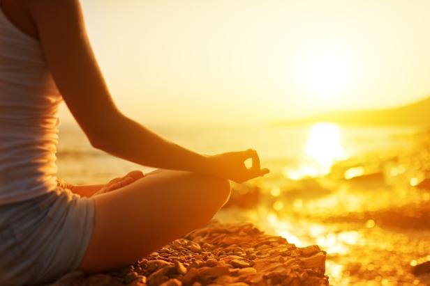 woman meditating cross-legged on beach in beautiful sunset
